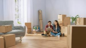 couple on apartment floor with packages around them